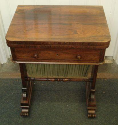 A late Regency rosewood needlework table, with hinged fold over top above a drawer and sliding pouch, on tapering end standards and trestle bases united by a turned stretchers, 56cm.