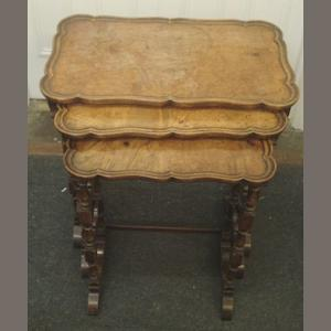 A nest of three reproduction walnut tables, with well figured shaped moulded edge tops, on baluster and square section dual end standards, the largest 60cm.