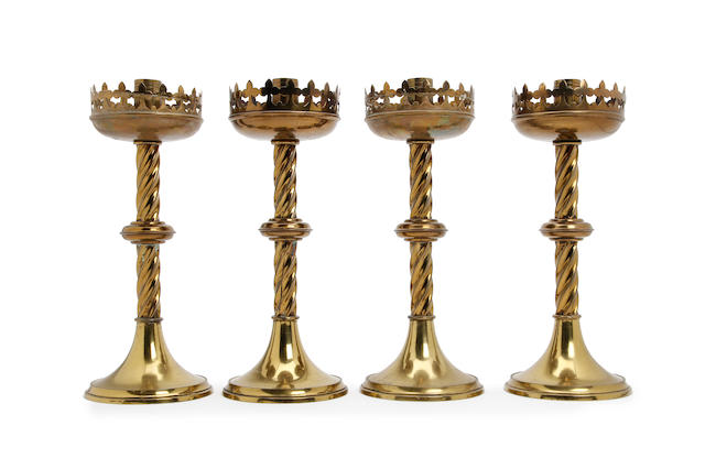 A set of four brass candlesticks, in the Gothic manner