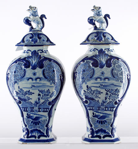Two Dutch delft vases and covers