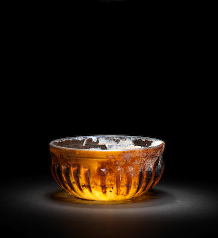 A Roman amber glass ribbed bowl