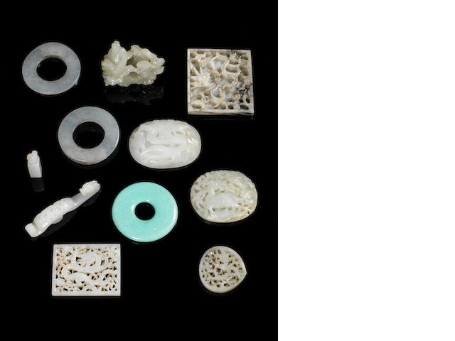 Jade/hardstone/ceramic items comprising ten pierced/carved plaques, four belt hooks/fasteners, two small seals, carved figure with tree root, eight other items, mounts/plaques, part belt hook, archers rings and two green ceramic items
