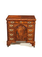 A George II walnut crossbanded and featherbanded kneehole desk