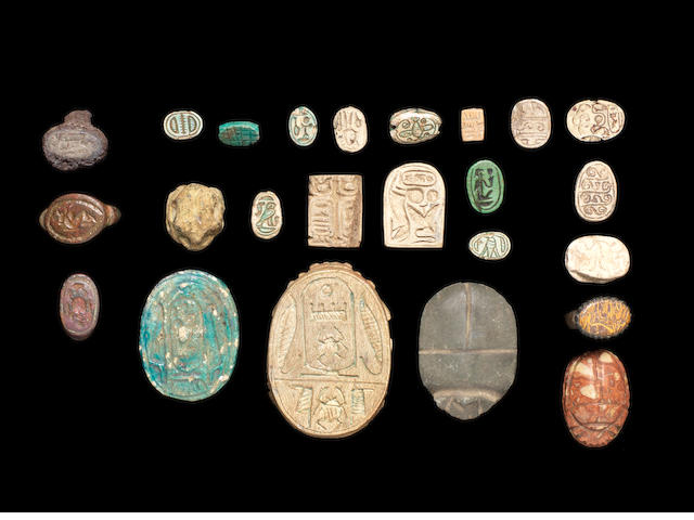 Twenty Egyptian scarabs and plaques  and four bronze rings 24