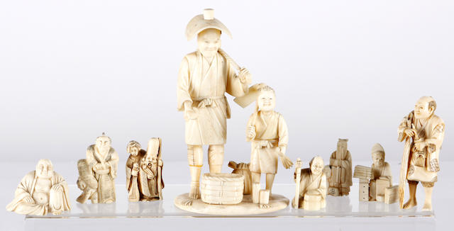 A Japanese Meiji period ivory okimono of a man and child, another of a craftsman, a carved Buddha and five netsukes