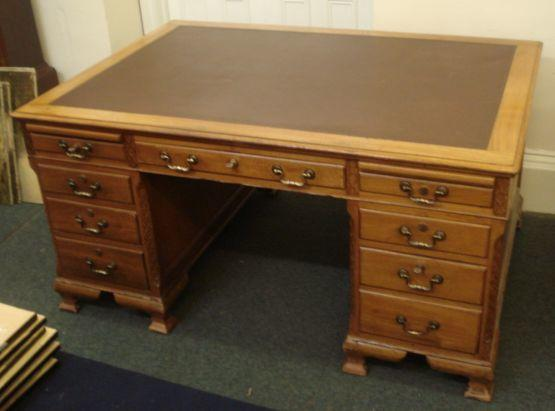 A reproduction George III style mahogany kneehole desk, the inset rectangular top above three frieze and five pedestal drawers disguised as six, fitted with slides, having blind cut card canted corners, on ogee feet, 153 x 106cm.