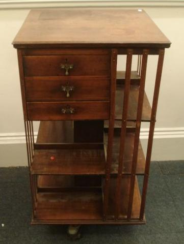An Edwardian walnut square revolving bookcase, having slatted sides and fitted with three short drawers, 59cm.