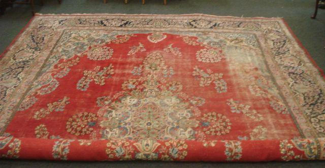 A Kirman carpet, with a large central ivory ground floral medallion, the red field with scattered floral sprays and indigo spandrels,4.2 x 2.05m.