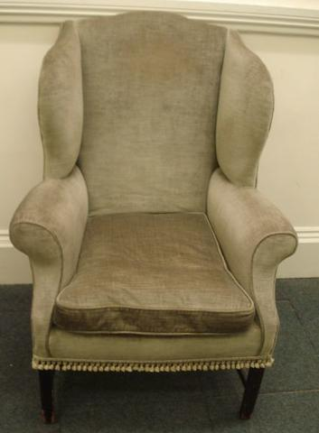 A George III style upholstered wing back armchair, on square legs united by stretchers.