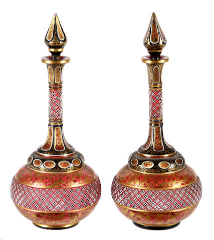 A pair of 19th Century Bohemian overlaid ruby glass gourd shape bottle vases, circa 1870, with two diamond cut and gilt leafy scroll bands, 16.5cm.