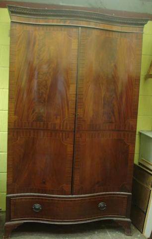 A George III style mahogany boxwood strung and crossbanded wardrobe, of serpentine outline, enclosed by a pair of doors, a drawer below, on shaped apron stand, 130cm.