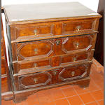An early 18th century panelled oak chest of four long drawers
