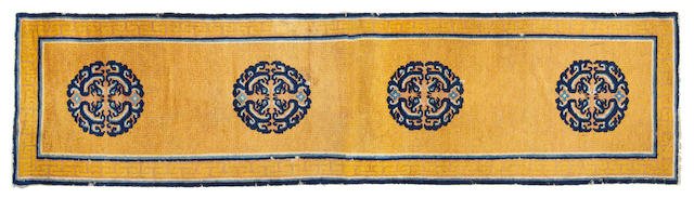 A pair of carpets with swastika frets and medallions on a yellow ground China, Circa 1800