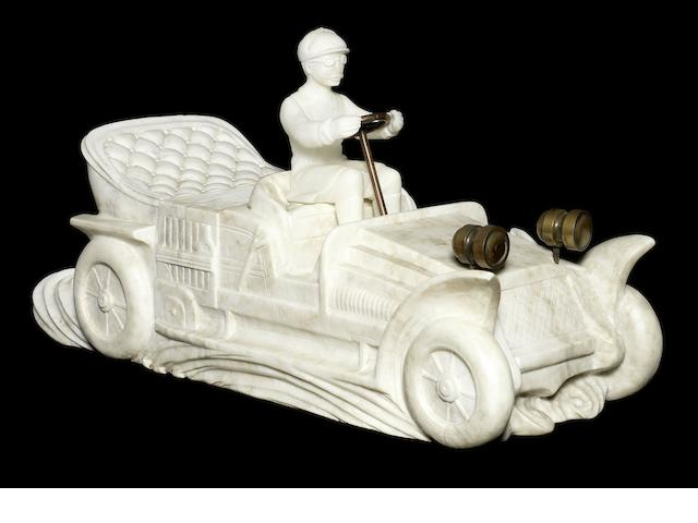 An alabaster statue of an early motorcar,