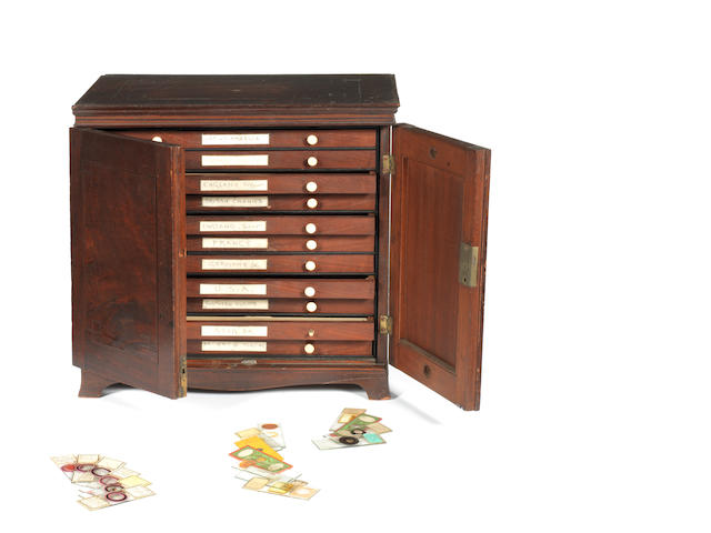 A mahogany slide cabinet with specimens from around the world,