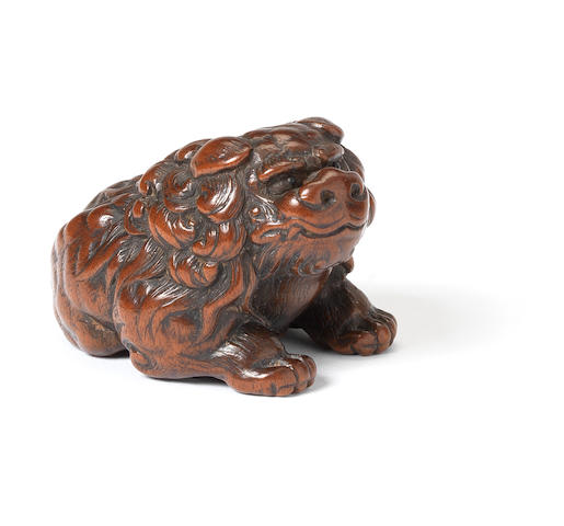 A boxwood netsuke of a shishi By Tomin, Tsu, early 19th century