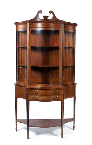 An Edwardian mahogany serpentine display cabinet on stand