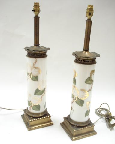 A pair of gilt metal and opaline glass cylindrical table lamps