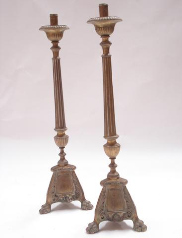 A pair of baroque style brass altar candle stands