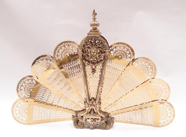 A 20th century pierced and cast brass folding fan-shaped fire guard