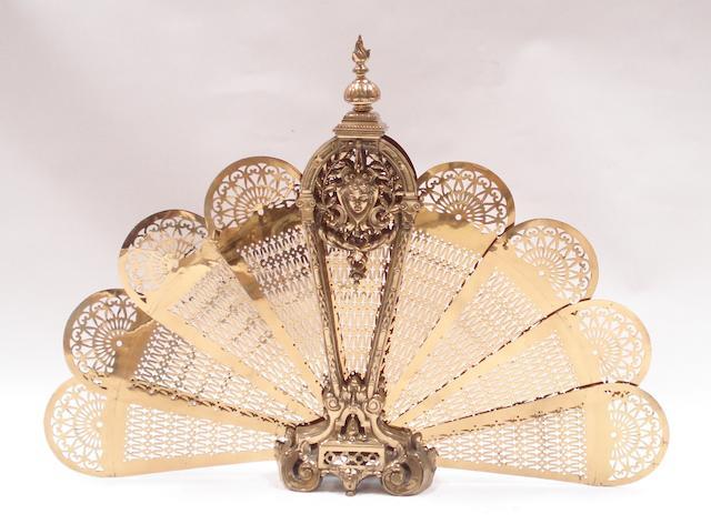 A 20th century pierced and cast brass folding fan-shaped fire guard