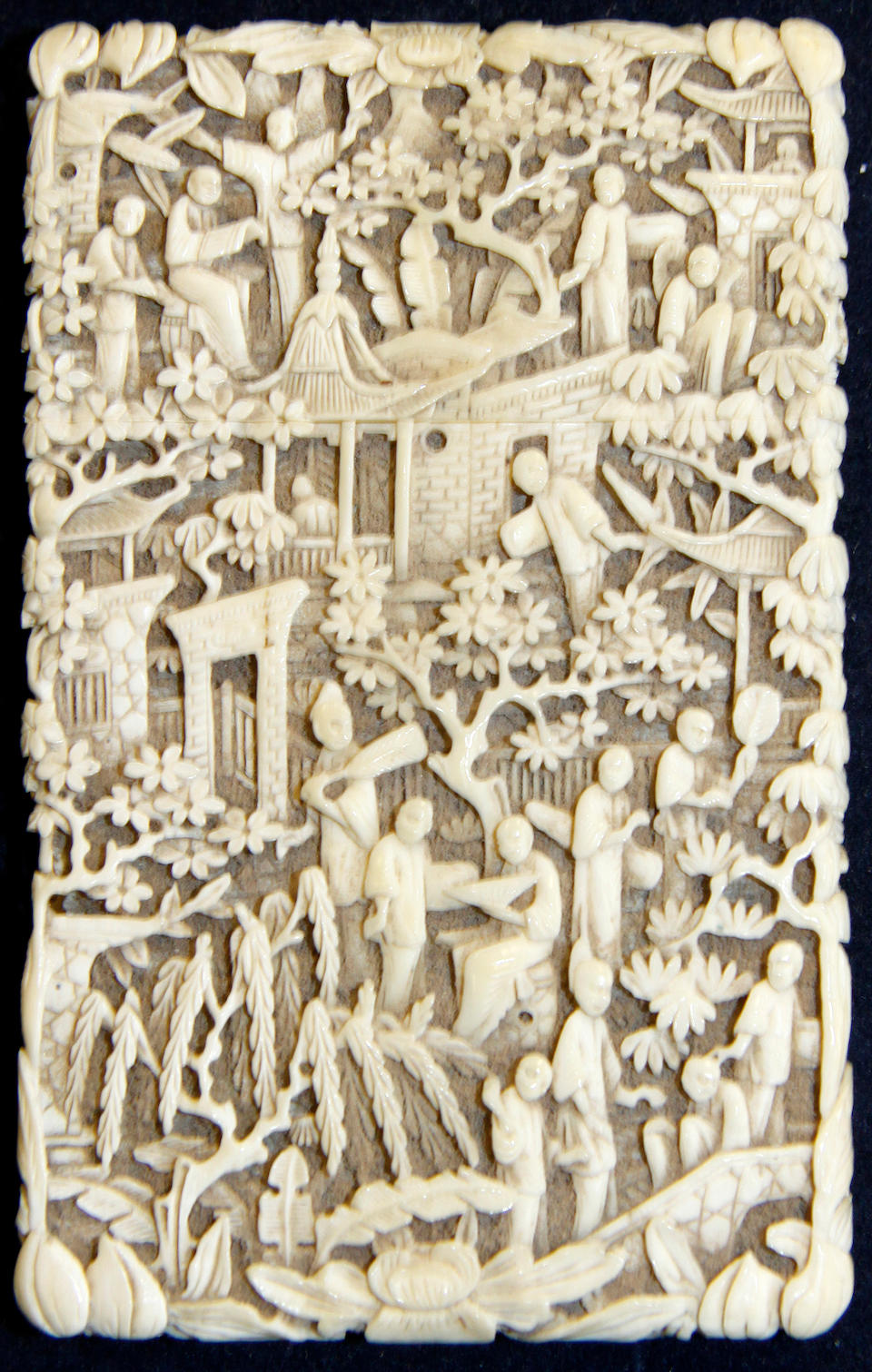 A Canton ivory card case, Qing dynasty, 19th Century, rectangular with pull-off cover, highly carved with figures amongst trees and buildings, 11cm.