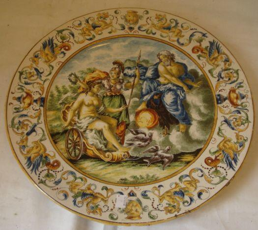 A 19th Century Italian Majolica charger, in the 16th Century manner, centrally painted with classical figures within an Italianate border, 43cm and two others similar, 46cm & 47cm diameter (3)