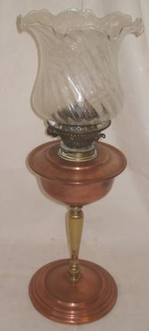 W A S Benson:  a copper and brass oil lamp, the baluster column on weighted circular base, later chimney and a reproduction shade, unmarked35cm.