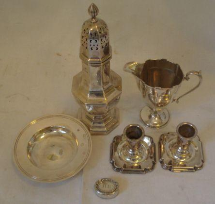 A silver caster, octagonal panelled form, pierced coarse with whorl finial by Elkington & Co, Birmingham 1939, a panelled cream jug with castellated rim on weighted foot, Birmingham 1914, a small Armada dish, 1973, a pair of table sticks with filled bases stamped 'Sterling Denmark', 6cm and an oval panel gilt pill box, 16ozs gross excluding table sticks.