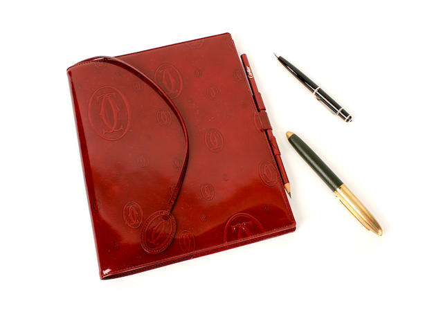 A Cartier journal and pen and a Louis Vuitton pen