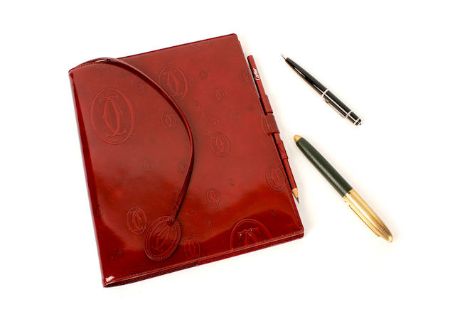 A Cartier journal and pen and a Louis Vuitton pen