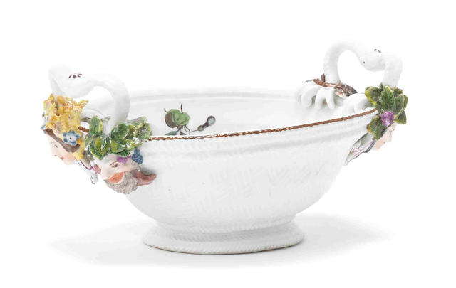 A Meissen oval basket, mask terminals, flowers inside