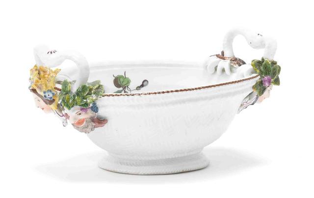A Meissen oval basket, mask terminals, flowers inside