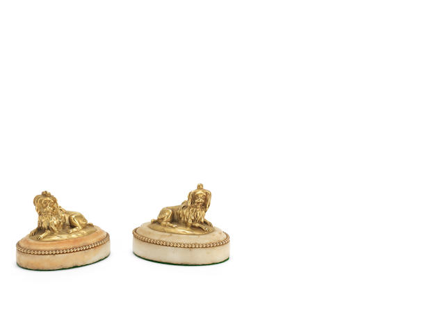 A pair of 19th century gilt bronze dogs on white marble bases