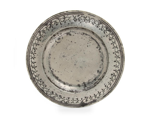 A fine and rare punch decorated broad-rim charger, circa 1690