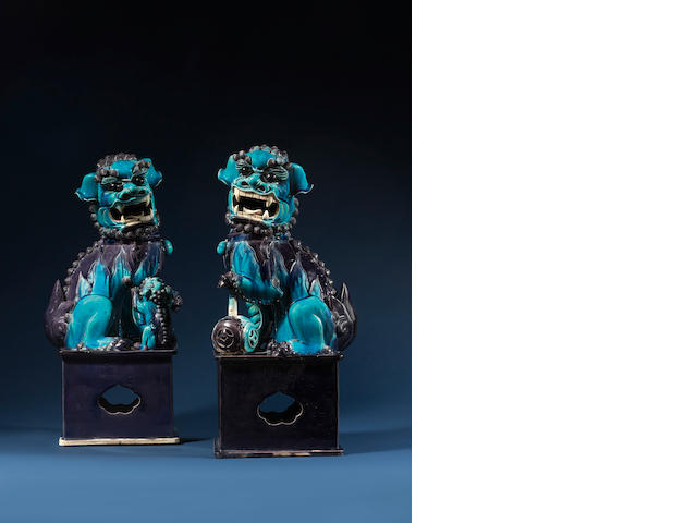 A very fine and large pair of turquoise and aubergine-glazed Buddhistic lions on plinths Kangxi