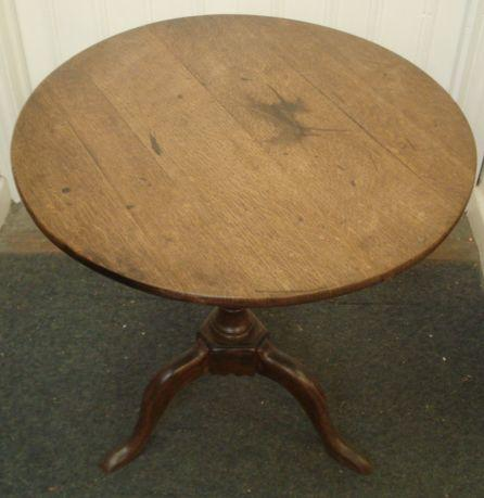 A 19th Century oak tea table, the circular tilt top on vase turned column and cabriole legs, 69cm diameter.