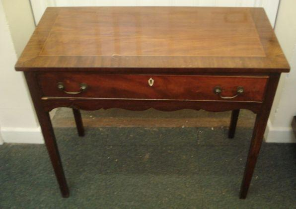 A George III mahogany side table, the rectangular crossbanded and chequer strung top above a frieze drawer and undulating apron, on square tapered legs, 92cm.