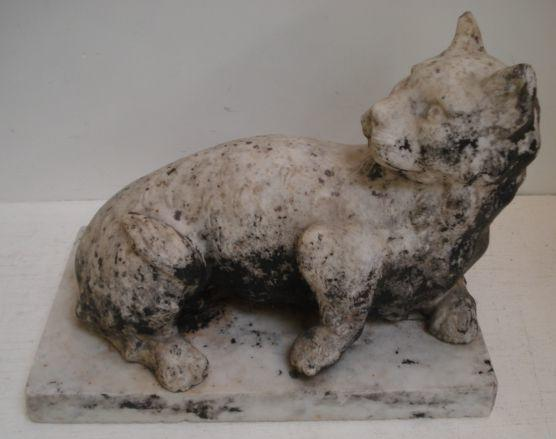 A 19th Century carved white marble figure, of a prowling small cat, it's head turned to one side, on a rectangular base, later painted finish to parts,38 x 23cm.