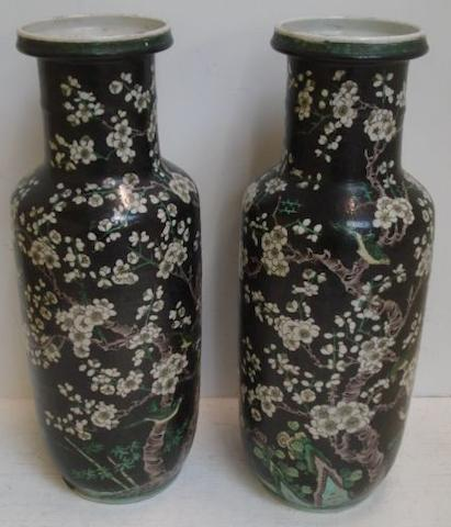 A pair of Chinese famille 'noir' rouleau vases, painted with birds amongst flowering trees, 46cm.
