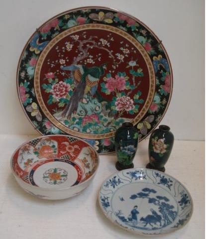 A pair of cloisonne enamel baluster vases, decorated with flowering rose branches on a green ground, 12cm, wood stands, a large 20th Century Japanese porcelain dish painted with a peacock and flowering branches, 40cm, a Hizen Imari floral painted bowl and a Chinese blue & white dish. (7)