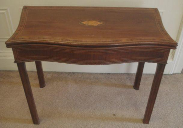 A George III mahogany rosewood crossbanded boxwood strung card table, of serpentine outline, the hinged fold over top inlaid with a conch shell oval, on moulded square chamfered legs, 90cm.
