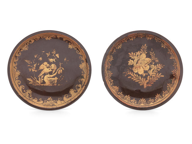 A pair of gilt decorated brown-ground porcelain saucers, soft paste with chips and wear