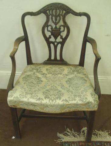 A George III mahogany open arm elbow chair, the foliate carved moulded frame with an arched back, the pierced vase shape splat centred by a classical urn, having a stuff over seat, on moulded square chamfered legs.