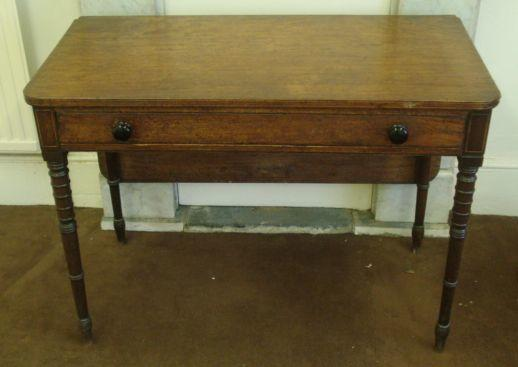 A Regency mahogany boxwood and ebony banded side table, originally a tea table with a hinged fold over top which has now been reversed, having a frieze drawer, on ring turned legs, 100cm.