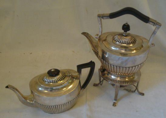 An Edwardian half gadrooned spirit kettle on stand, with spirit burner, blackwood handles by Goldsmiths & Silversmiths, 1911, and a half gadrooned teapot by a different maker, 1911, 42ozs total.