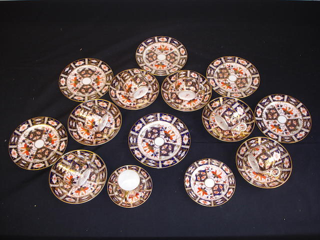 A Royal Crown Derby tea service of six settings including cup, saucer and side plate, together with a small coffee can, saucer and plate