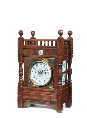 A 19th century Aesthetic Movement oak, gilt metal and porcelain mounted mantel clock in the style of Lewis Foreman Day