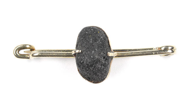 AMUNDSEN (ROALD) - BROOCH A gold pin brooch with an unidentified black, collet set stone to the centre, presumed to have been taken by Amundsen from the South Pole