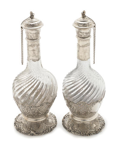 A pair of late 19th century Dutch silver mounted decanters, of spiral twist baluster form raised on pierced spreading circular  feet with floral catouches in relief - Height 30cms (2)